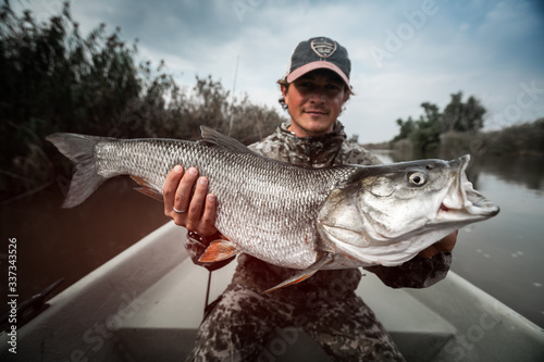Photo Angler sits in the boat and holds the trophy Asp fish