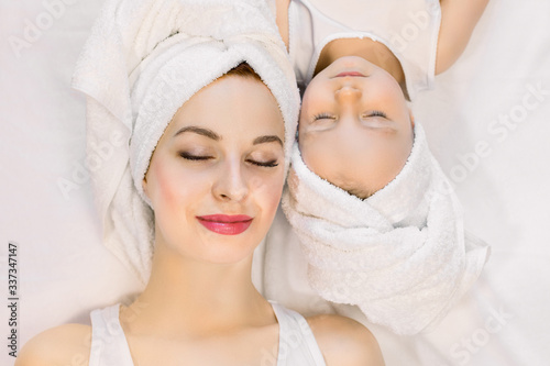 Fototapety, obrazy: Top view of beautiful young mother and her two year old daughter lying on the bed at home, relaxing after nice spa bath procedures with eyes closed. Family spa and beauty care
