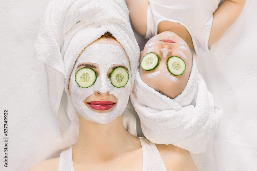 Fototapeta Mother and little daughter having spa procedures together. They are in white bath towels on head and with slices of cucumber on their eyes. Woman has white facial mask on her skin