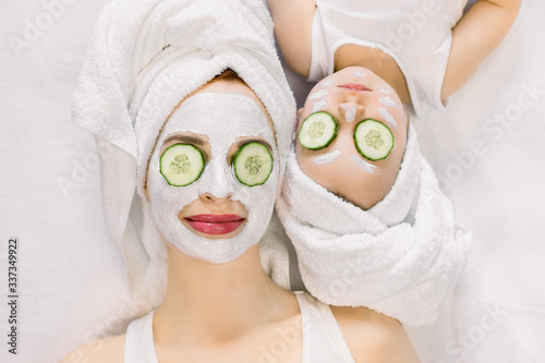 Fototapety, obrazy: Mother and little daughter having spa procedures together. They are in white bath towels on head and with slices of cucumber on their eyes. Woman has white facial mask on her skin