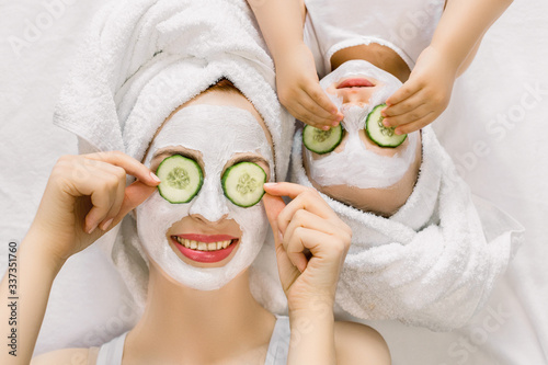 Fototapety, obrazy: Photo of cheerful mother and little daughter with wrapped hair in white bath towels, white facial mud mask on faces, lying on the bed, and applying pieces of cucumber to their eyes. Family spa