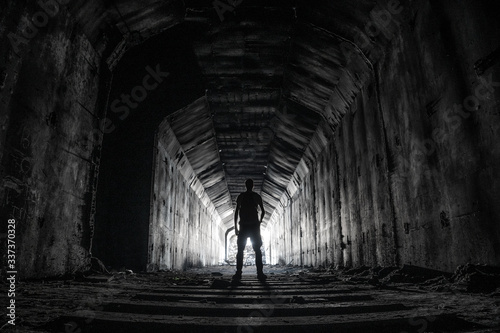Photo Shilouette of human underground explorer in abandoned dark tunnel with light in the end