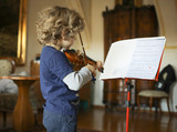 A little boy plays the violin at home. The child learns music.