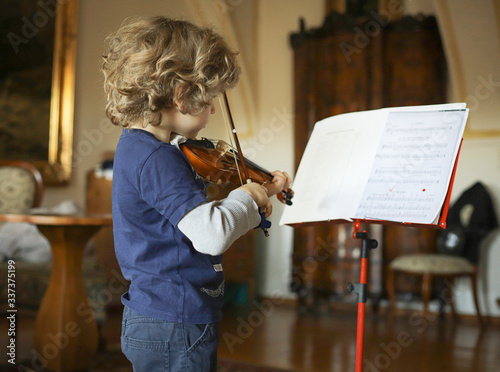 Fotografie, Obraz A little boy plays the violin at home. The child learns music.