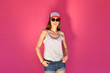 Leinwanddruck Bild - Sexy young woman in hip hop style clothes and sunglasses posing against a pink wall background