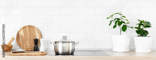 Fototapeta White modern kitchen interior with wooden worktop and kitchenware, culinary conc