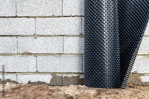 Valokuva basement wall waterproofing - installing dimple geomembrane