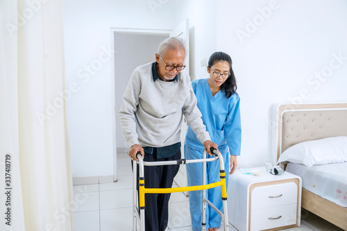 Fototapeta Nurse helping old man to walk with walker equipment obraz