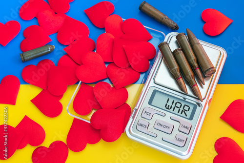 Gun cartridges and red hearts on scales on blue yellow background close up Wallpaper Mural