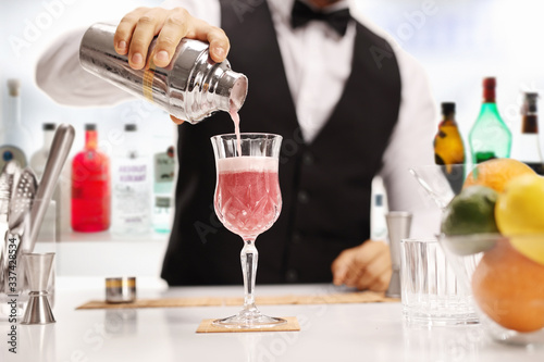 Photo Bartender pouring a cocktail in a glass