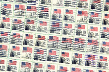 Set Of USA Postage Stamps With USA Flag As Background.
