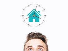 Time To Stay At Home Concept. Young Man Eyes Looking Up To A Clock With House Icon