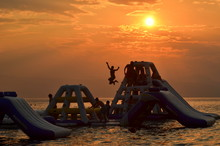 People On Jungle Gym On Sea Against Sky During Sunset