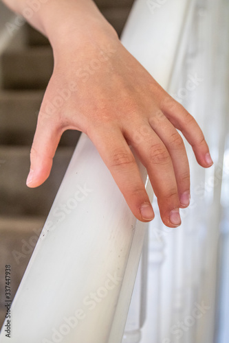 hand reaches for and grabs white stair bannister Wallpaper Mural
