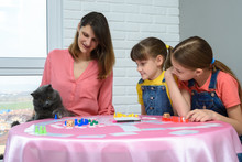 The Family Watches As The Cat Plays A Chip From The Table From The Board Game