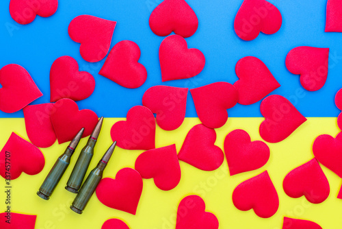 Gun cartridges and red hearts on colorful blue yellow background flat lay close up Canvas Print