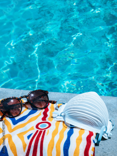 Fotografía Face mask, a towel and a pair of sunglasses laying beside a swimming pool