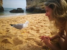 Young Woman Looking At Seagull...