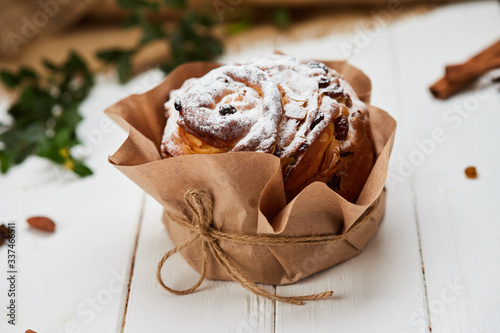 Tela Easter cake decorated by raisins and icing sugar on white wooden background, Tra