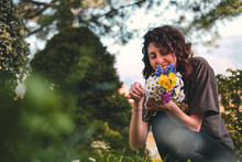 Beautiful And Happy Girl Collect Colorful Bouquest Of Spring Daisies Flowers In A Green Park, Environment And Ecology Theme