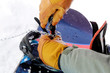 Close up on young man repairing snowboard. Winter mountain holiday.