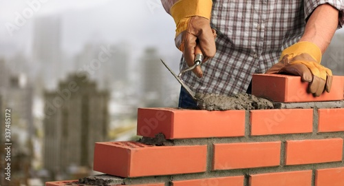 Fotomural Man worker installing brick masonry wall with a trowel