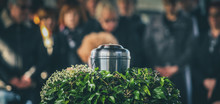 A Metal Urn With Ashes Of A Dead Person On A Funeral, With People Mourning In The Background On A Memorial Service. Sad Grieving Moment At The End Of A Life. Last Farewell To A Person In An Urn.