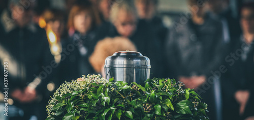 Photo A metal urn with ashes of a dead person on a funeral, with people mourning in the background on a memorial service