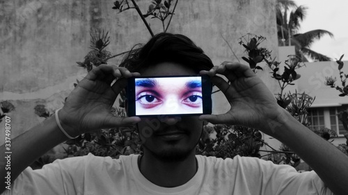 Naklejka premium Optical Illusion Of Man Displaying Photograph On Mobile Phone Against Face