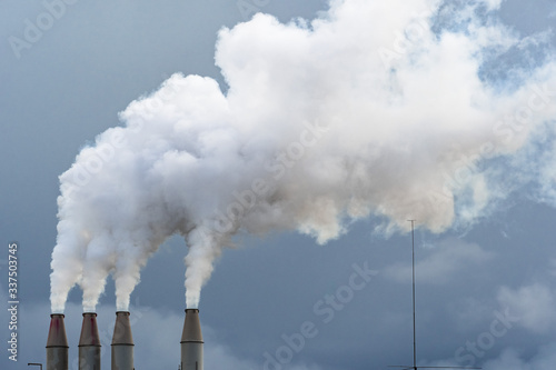 Fotografiet Smoke and steam rising into the air from power plant stacks; dark clouds backgro