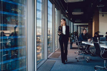 Serious female administrative manager in formal suit walking in office with digital tablet for checking office working process, confident woman business owner looking at window passing with touchpad