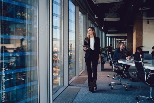Fotomural Serious female administrative manager in formal suit walking in office with digi