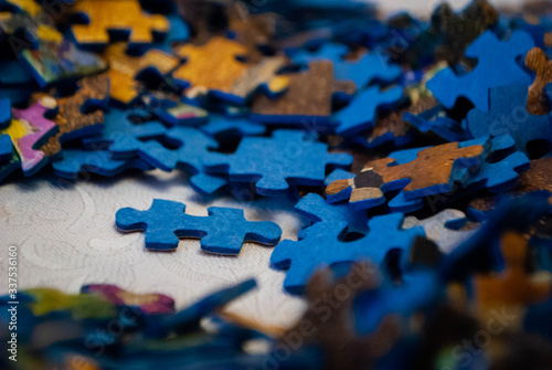 Fototapeta Close-up of colorful pieces of puzzle. One standing puzzle piece on the table. Stack of Puzzle Pieces. Puzzle pieces. Puzzle figures. Puzzle for fun.  obraz