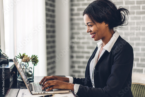 Fotomural Portrait of smiling happy african american black woman relaxing using technology of laptop computer while sitting on table