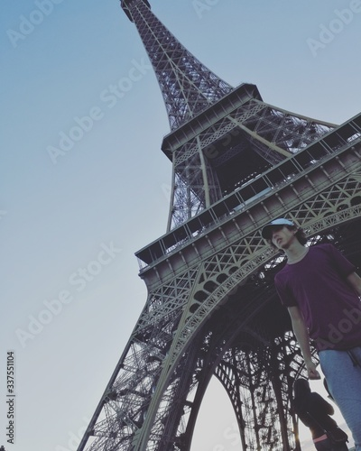 Low Angle View Of Man Standing Against Eiffel Tower #337551104