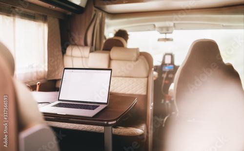 Valokuva Freelancer nomad tele working inside camper van caravan online location independent lifestyle telework and travel, away from home workplace office campervan