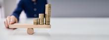 Businessperson Balancing Coins...