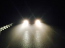 Illuminated Headlights On Street At Night