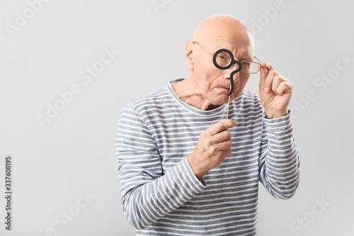 Obraz na plátně Portrait of elderly man with party decor on grey background