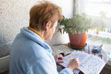 Senior Woman Doing Crossword Puzzles And Hobbies