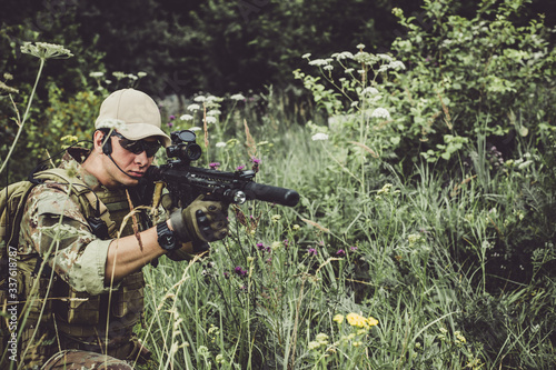 Fotografía A military man or airsoft player in a camouflage suit sits in the grass and aims