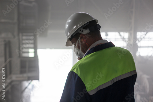 Mining engineer in yellow-blue uniform and white helmet and respirator inspects Fototapeta