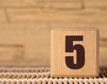A Wooden Cube With The Number Five On A Beige Background.