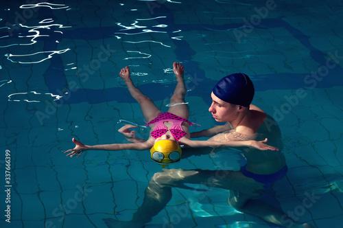 Photo Swimming pool coach teaches a little girl to swim