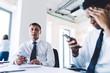 Multiethnic business people using smartphones in workplace