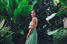 Smiling Asian Woman In Romantic Dress Standing Against Lush Foliage