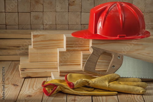 Photographie construction carpentry tools red helmet glaves and handsaw on wooden background