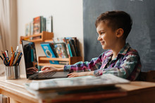 Cute Boy Schoolboy Sitting At A Desk In His Room And Studying Remotely From His Home