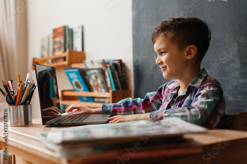 Fototapeta cute boy schoolboy sitting at a desk in his room and studying remotely from his