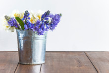 Bouquet Of Blue Hyacinths And White Daffodils In Rustic Bucket On Wooden Table And White Background. Space For Text